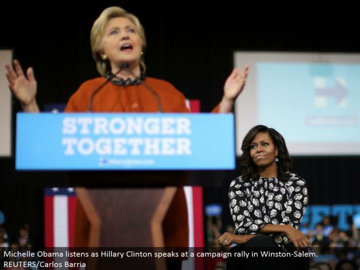 Michelle Obama listens as Hillary Clinton talks at a battle rally in Winston-Salem. REUTERS/Carlos Barria