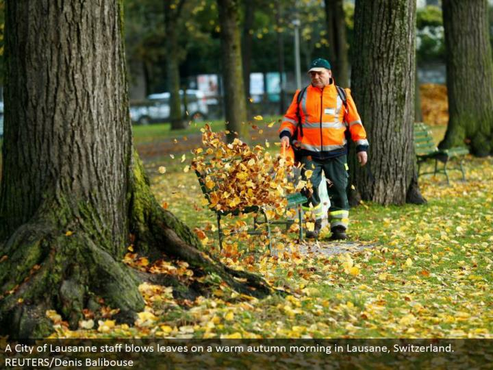 A City of Lausanne staff blows leaves on a warm fall morning in Lausane, Switzerland. REUTERS/Denis Balibouse