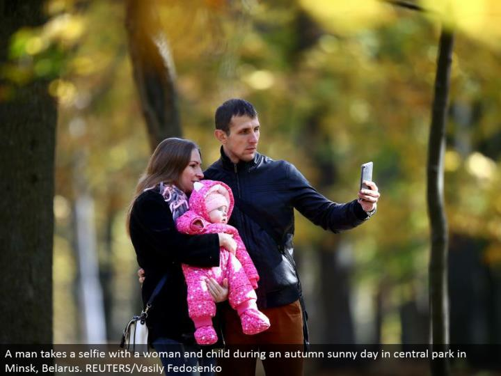 A man brings a selfie with a lady and tyke amid a harvest time sunny day in focal stop in Minsk, Belarus. REUTERS/Vasily Fedosenko