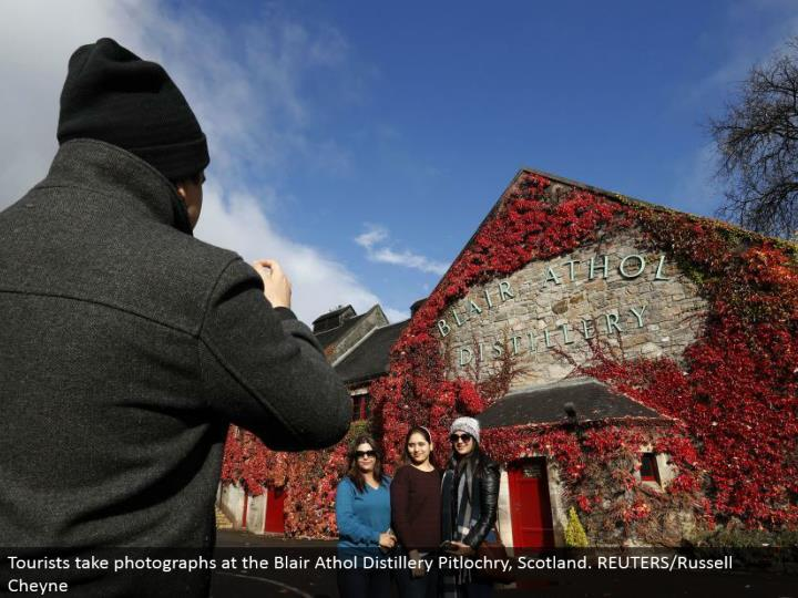 Tourists take photos at the Blair Athol Distillery Pitlochry, Scotland. REUTERS/Russell Cheyne
