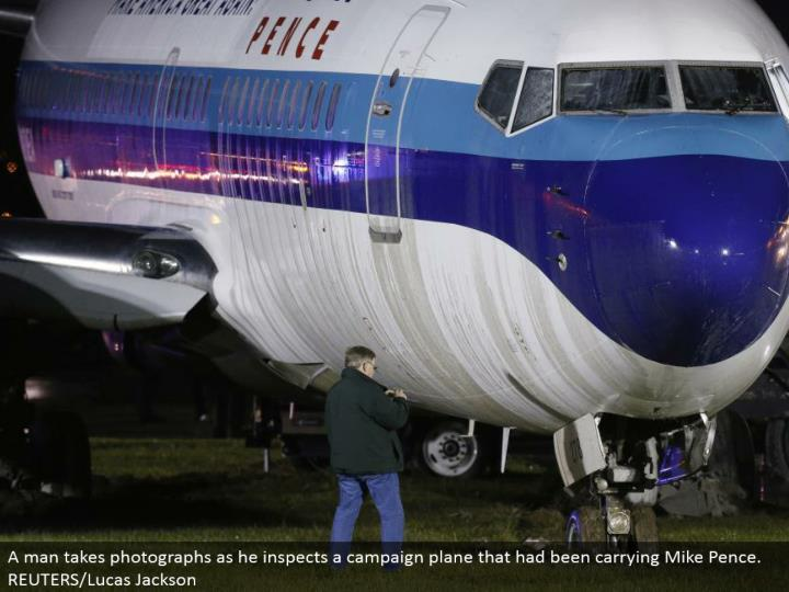 A man takes photos as he investigates a crusade plane that had been conveying Mike Pence. REUTERS/Lucas Jackson