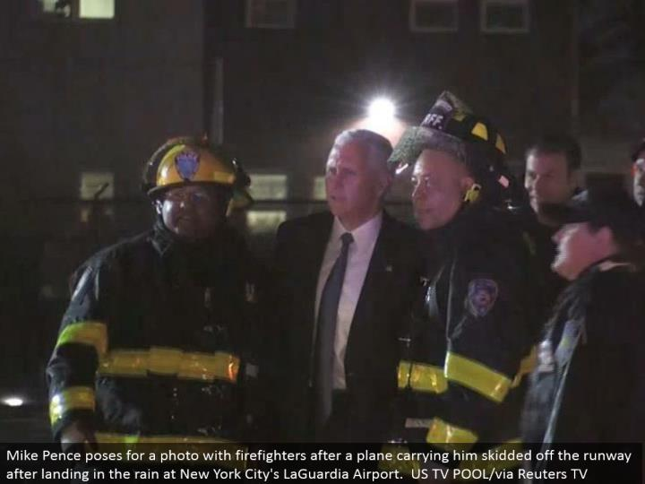 Mike Pence postures for a photograph with firefighters after a plane carting him slid away the runway subsequent to arriving in the rain at New York City's LaGuardia Airport. US TV POOL/by means of Reuters TV