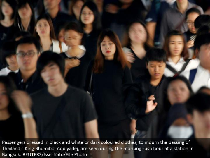 Passengers wearing high contrast or dim hued garments, to grieve the death of Thailand's King Bhumibol Adulyadej, are seen amid the morning surge hour at a station in Bangkok. REUTERS/Issei Kato/File Photo
