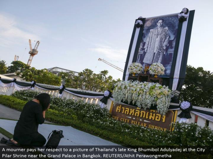 A griever offers her regard to a photo of Thailand's late King Bhumibol Adulyadej at the City Pilar Shrine close to the Grand Palace in Bangkok. REUTERS/Athit Perawongmetha