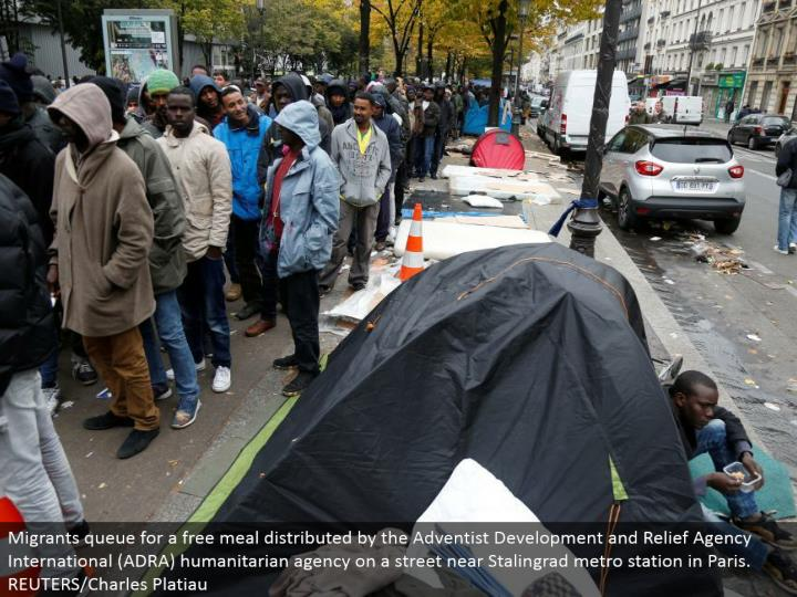 Migrants line for a free dinner conveyed by the Adventist Development and Relief Agency International (ADRA) helpful office on a road close Stalingrad metro station in Paris. REUTERS/Charles Platiau
