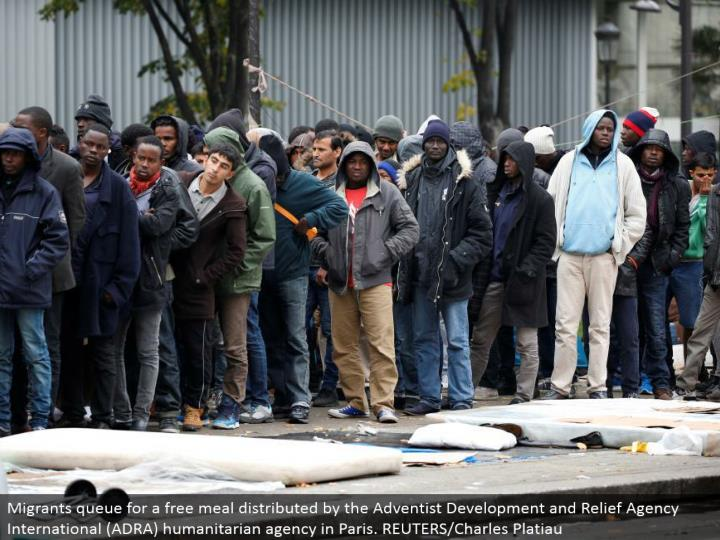 Migrants line for a free feast appropriated by the Adventist Development and Relief Agency International (ADRA) compassionate office in Paris. REUTERS/Charles Platiau