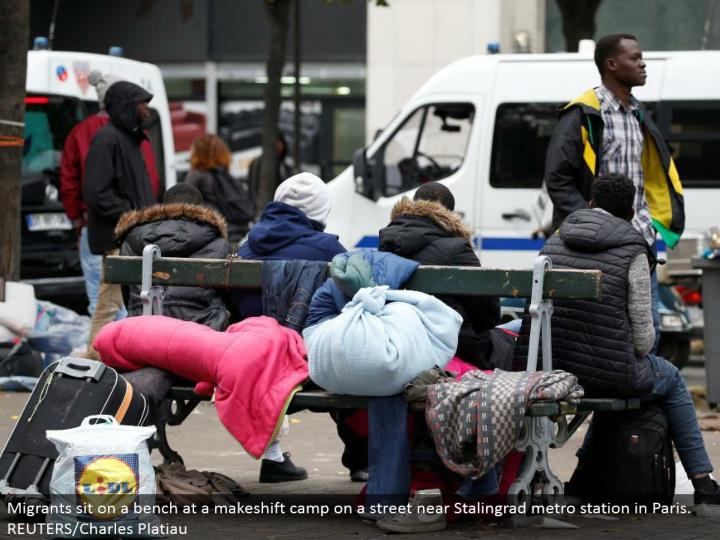 Migrants sit on a seat at a stopgap camp on a road close Stalingrad metro station in Paris. REUTERS/Charles Platiau