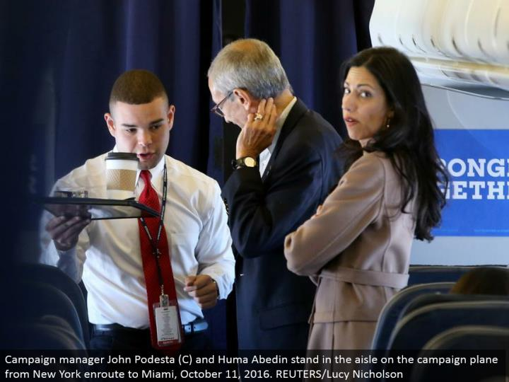 Campaign administrator John Podesta (C) and Huma Abedin remain in the path on the battle plane from New York enroute to Miami, October 11, 2016. REUTERS/Lucy Nicholson