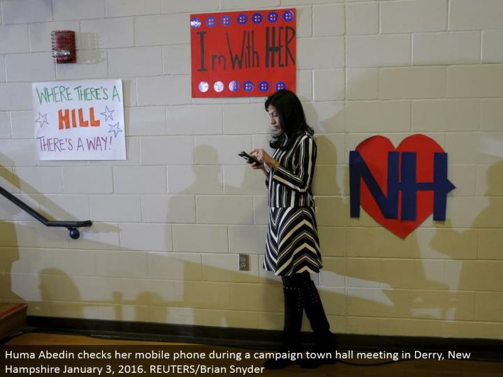 Huma Abedin checks her cell phone amid a battle town lobby meeting in Derry, New Hampshire January 3, 2016. REUTERS/Brian Snyder