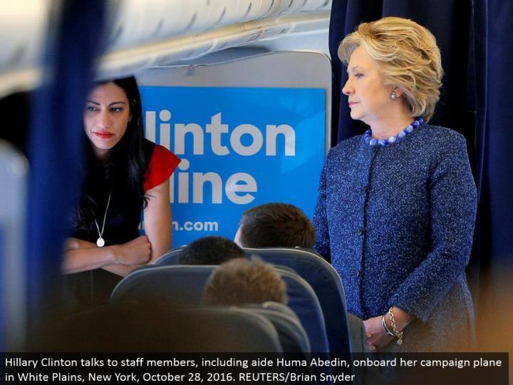 Hillary Clinton converses with staff individuals, including associate Huma Abedin, locally available her crusade plane in White Plains, New York, October 28, 2016. REUTERS/Brian Snyder