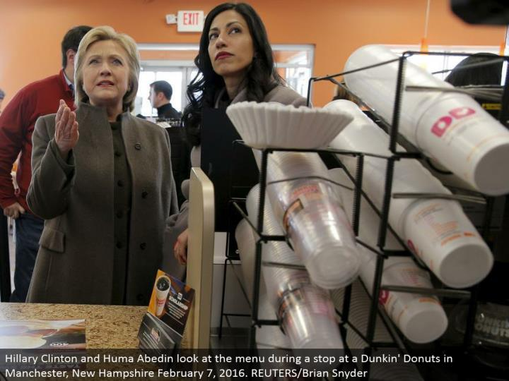 Hillary Clinton and Huma Abedin take a gander at the menu amid a stop at a Dunkin' Donuts in Manchester, New Hampshire February 7, 2016. REUTERS/Brian Snyder