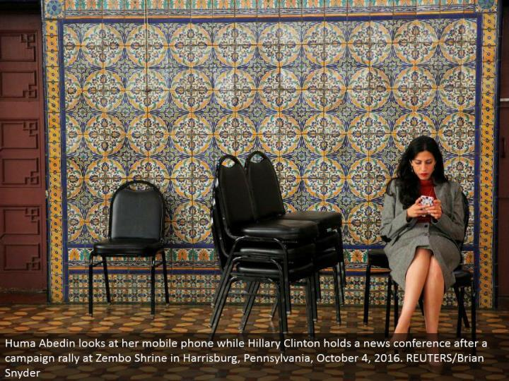Huma Abedin takes a gander at her cell phone while Hillary Clinton holds a news gathering after a battle rally at Zembo Shrine in Harrisburg, Pennsylvania, October 4, 2016. REUTERS/Brian Snyder