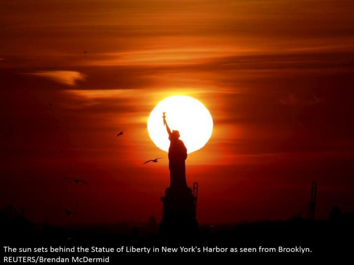 The sun sets behind the Statue of Liberty in New York's Harbor as observed from Brooklyn. REUTERS/B...