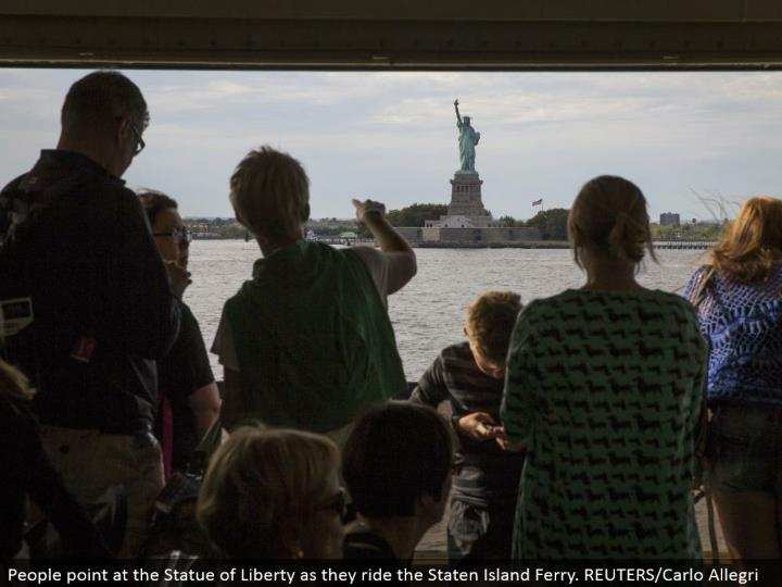 People point at the Statue of Liberty as they ride the Staten Island Ferry. REUTERS/Carlo Allegri