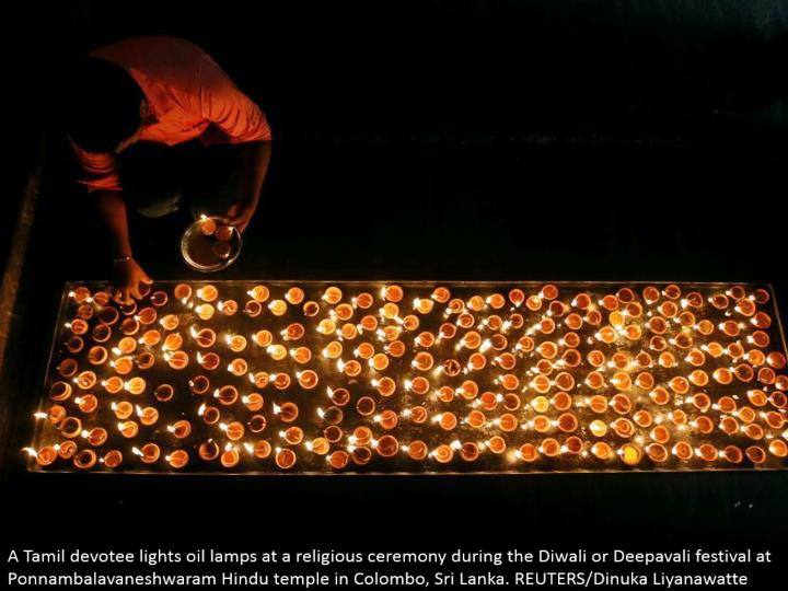 A Tamil aficionado lights oil lights at a religious service amid the Diwali or Deepavali celebration at Ponnambalavaneshwaram Hindu sanctuary in Colombo, Sri Lanka. REUTERS/Dinuka Liyanawatte