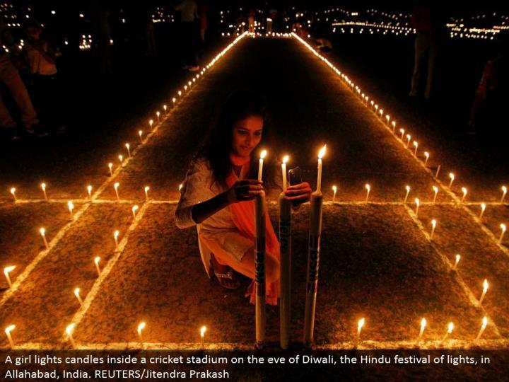A young lady lights candles inside a cricket stadium on the eve of Diwali, the Hindu celebration of lights, in Allahabad, India. REUTERS/Jitendra Prakash