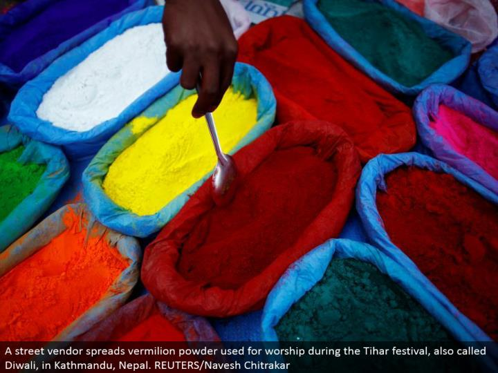 A road merchant spreads vermilion powder utilized for love amid the Tihar celebration, additionally called Diwali, in Kathmandu, Nepal. REUTERS/Navesh Chitrakar