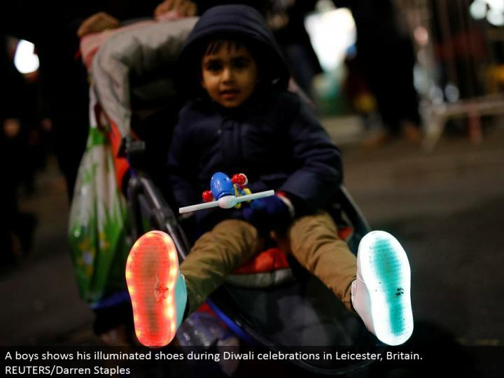 A young men demonstrates his lit up shoes amid Diwali festivities in Leicester, Britain. REUTERS/Darren Staples