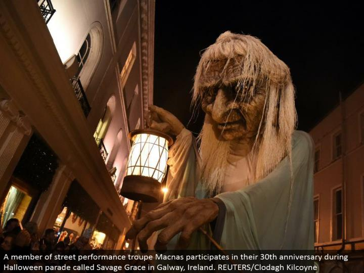 A individual from road execution troupe Macnas takes an interest in their 30th commemoration amid Halloween parade called Savage Grace in Galway, Ireland. REUTERS/Clodagh Kilcoyne