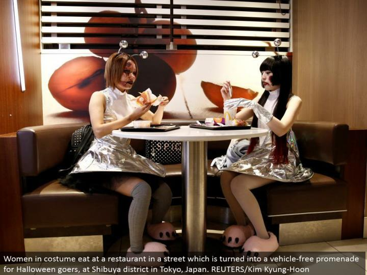 Women in outfit eat at an eatery in a road which is transformed into a without vehicle promenade for Halloween goers, at Shibuya area in Tokyo, Japan. REUTERS/Kim Kyung-Hoon