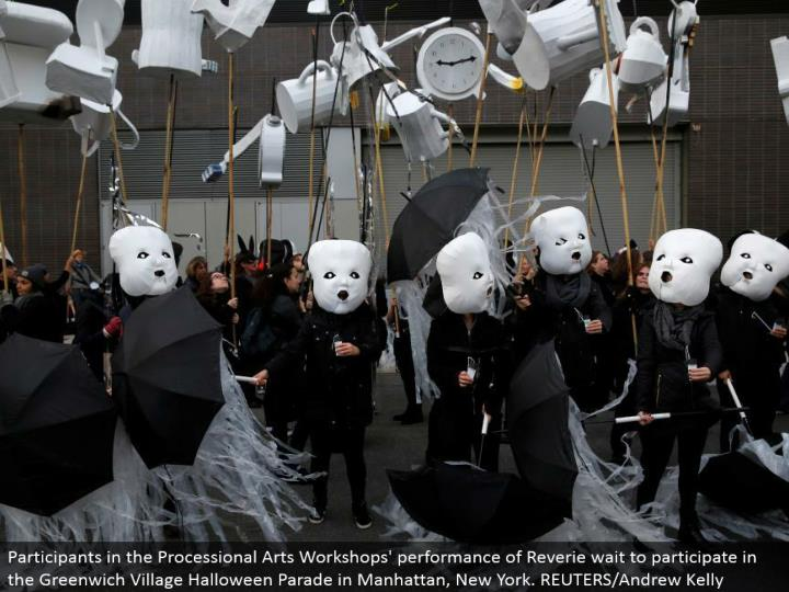 Participants in the Processional Arts Workshops' execution of Reverie hold up to take an interest in the Greenwich Village Halloween Parade in Manhattan, New York. REUTERS/Andrew Kelly