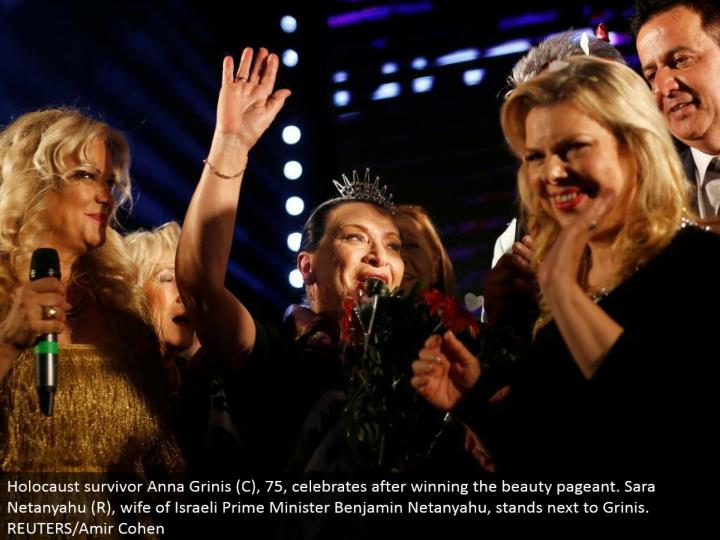 Holocaust survivor Anna Grinis (C), 75, celebrates in the wake of winning the excellence exhibition. Sara Netanyahu (R), spouse of Israeli Prime Minister Benjamin Netanyahu, remains beside Grinis. REUTERS/Amir Cohen
