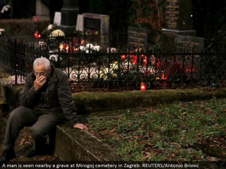 A man is seen close-by a grave at Mirogoj graveyard in Zagreb. REUTERS/Antonio Bronic