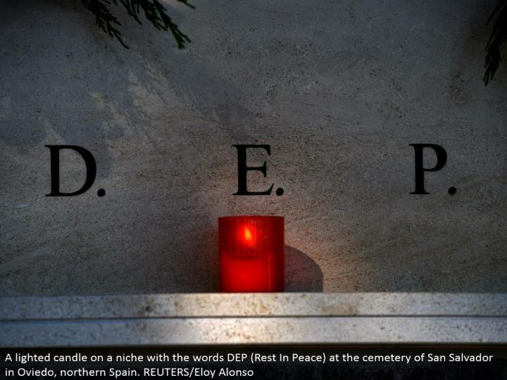 A lit light on a specialty with the words DEP (Rest In Peace) at the burial ground of San Salvador in Oviedo, northern Spain. REUTERS/Eloy Alonso