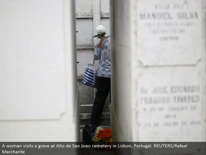 A lady visits a grave at Alto de Sao Joao graveyard in Lisbon, Portugal. REUTERS/Rafael Marchante