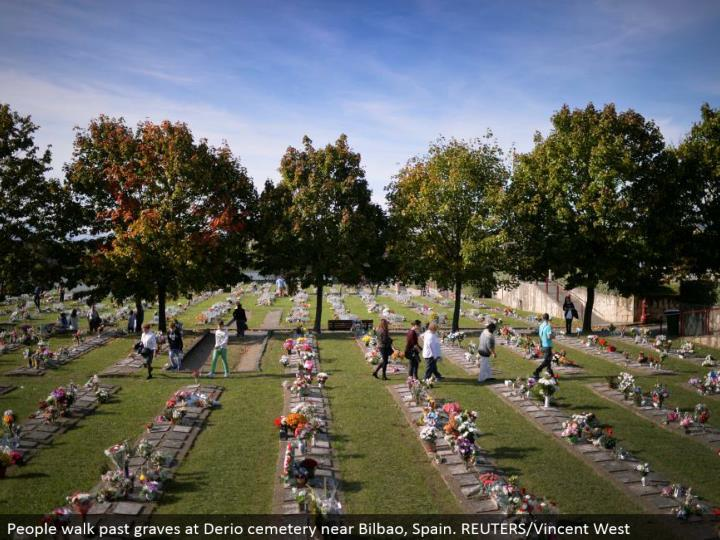 People stroll past graves at Derio burial ground close Bilbao, Spain. REUTERS/Vincent West