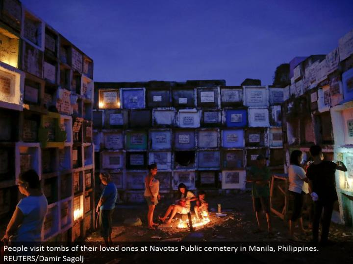People visit tombs of their friends and family at Navotas Public graveyard in Manila, Philippines. REUTERS/Damir Sagolj