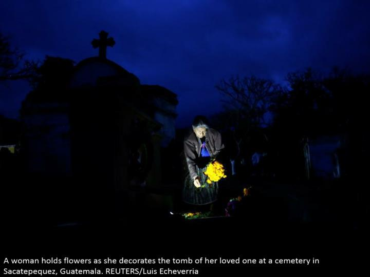 A lady holds blooms as she enriches the tomb of her adored one at a burial ground in Sacatepequez, Guatemala. REUTERS/Luis Echeverria