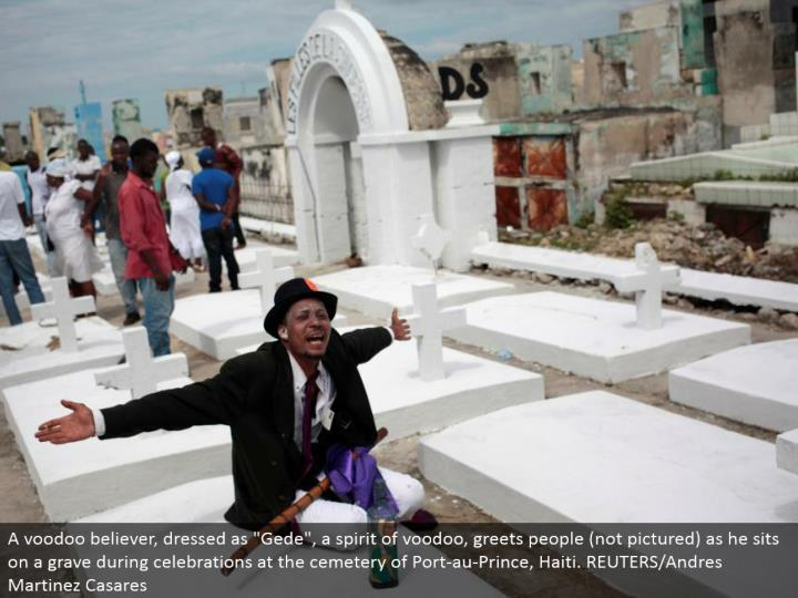 "A voodoo devotee, dressed as ""Gede"", a soul of voodoo, welcomes individuals (not imagined) as he sits on a grave amid festivities at the graveyard of Port-au-Prince, Haiti. REUTERS/Andres Martinez Casares"