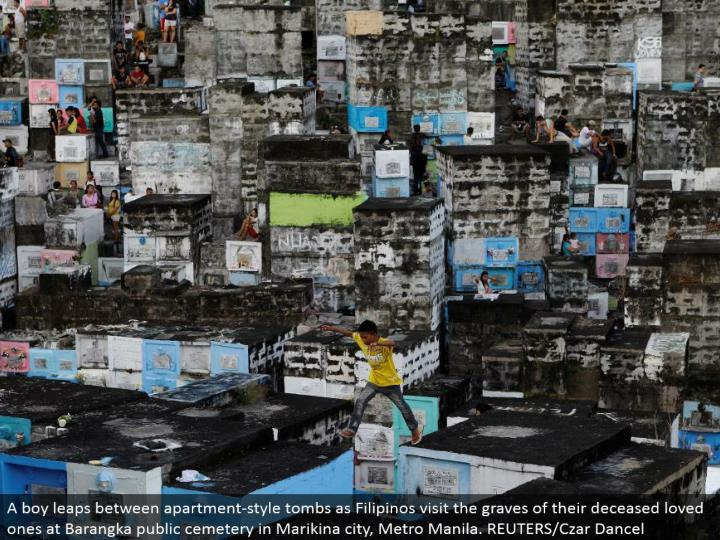 A kid jumps between condo style tombs as Filipinos visit the graves of their expired friends and family at Barangka open burial ground in Marikina city, Metro Manila. REUTERS/Czar Dancel