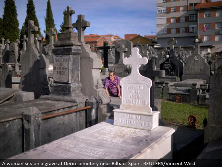 A lady sits on a grave at Derio burial ground close Bilbao, Spain. REUTERS/Vincent West