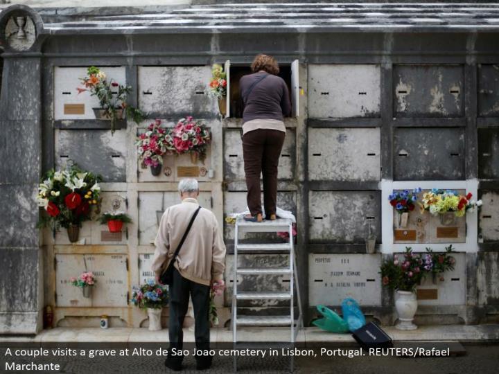 A couple visits a grave at Alto de Sao Joao burial ground in Lisbon, Portugal. REUTERS/Rafael Marchante
