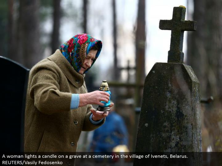 A lady lights a flame on a grave at a burial ground in the town of Ivenets, Belarus. REUTERS/Vasily Fedosenko