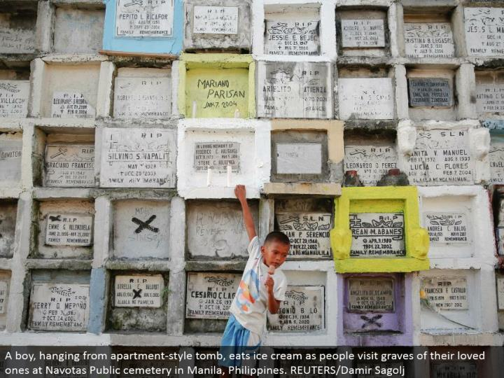 A kid, swinging from loft style tomb, eats frozen yogurt as individuals visit graves of their friends and family at Navotas Public graveyard in Manila, Philippines. REUTERS/Damir Sagolj