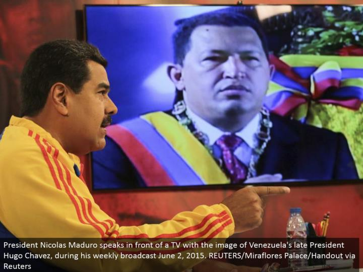 President Nicolas Maduro talks before a TV with the picture of Venezuela's late President Hugo Chavez, amid his week after week communicate June 2, 2015. REUTERS/Miraflores Palace/Handout by means of Reuters