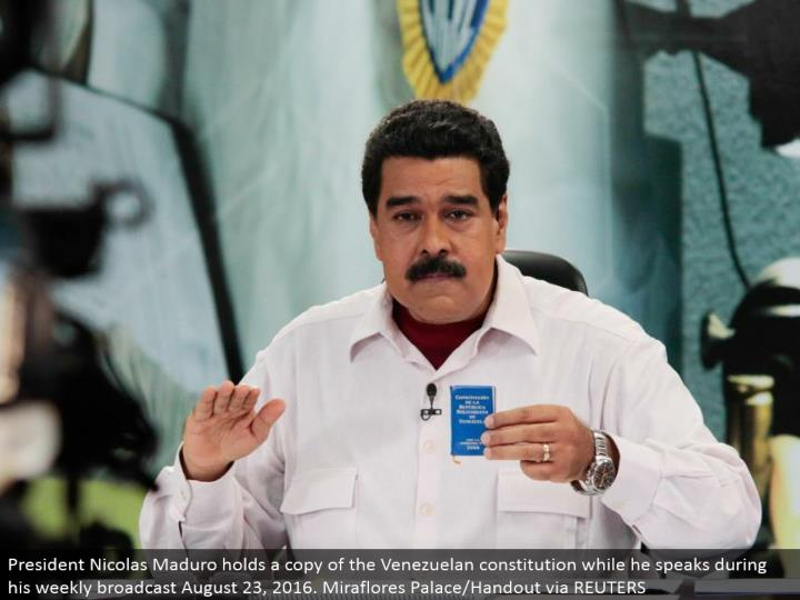 President Nicolas Maduro holds a duplicate of the Venezuelan constitution while he talks amid his week by week communicate August 23, 2016. Miraflores Palace/Handout through REUTERS