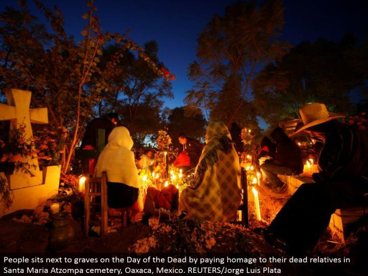 People sits by graves on the Day of the Dead by paying praise to their dead relatives in Santa Maria Atzompa graveyard, Oaxaca, Mexico. REUTERS/Jorge Luis Plata
