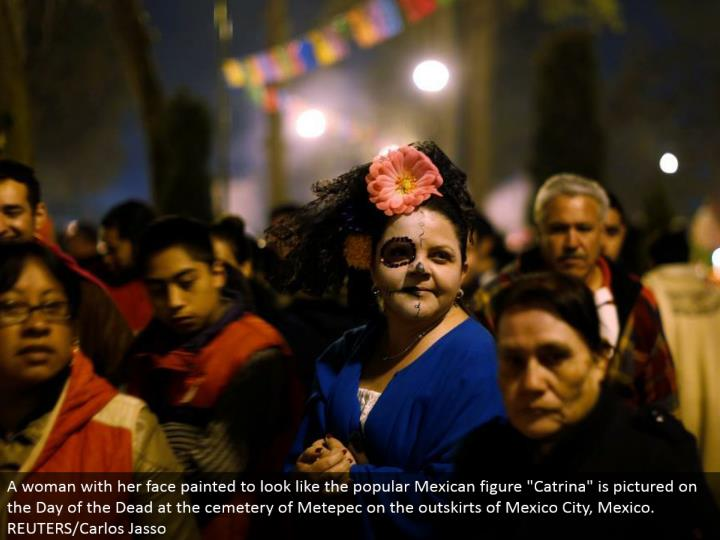 "A lady with her face painted to resemble the mainstream Mexican figure ""Catrina"" is envisioned on the Day of the Dead at the graveyard of Metepec on the edges of Mexico City, Mexico. REUTERS/Carlos Jasso"