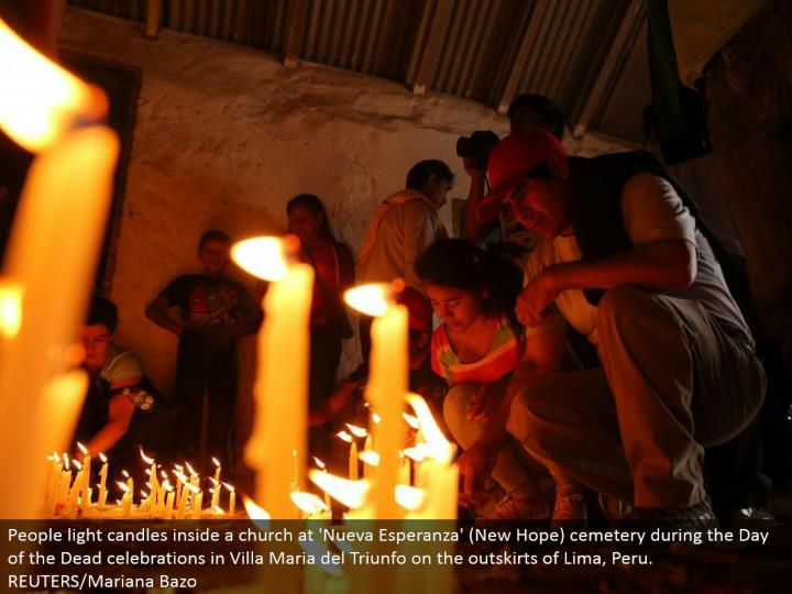 People light candles inside a congregation at 'Nueva Esperanza' (New Hope) graveyard amid the Day of the Dead festivals in Villa Maria del Triunfo on the edges of Lima, Peru. REUTERS/Mariana Bazo
