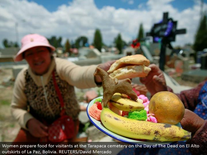 Women plan sustenance for visitants at the Tarapaca burial ground on the Day of The Dead on El Alto edges of La Paz, Bolivia. REUTERS/David Mercado