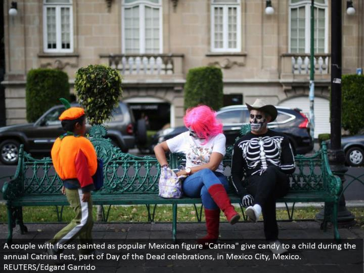 "A couple with appearances painted as prominent Mexican figure ""Catrina"" offer treat to a tyke amid the yearly Catrina Fest, a portion of Day of the Dead festivals, in Mexico City, Mexico. REUTERS/Edgard Garrido"