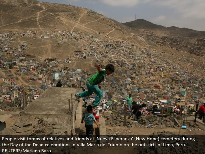 People visit tombs of relatives and companions at 'Nueva Esperanza' (New Hope) graveyard amid the Day of the Dead festivals in Villa Maria del Triunfo on the edges of Lima, Peru. REUTERS/Mariana Bazo