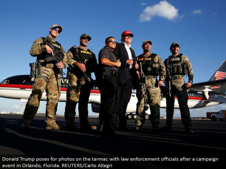 Donald Trump postures for photographs on the landing area with law implementation authorities after a crusade occasion in Orlando, Florida. REUTERS/Carlo Allegri