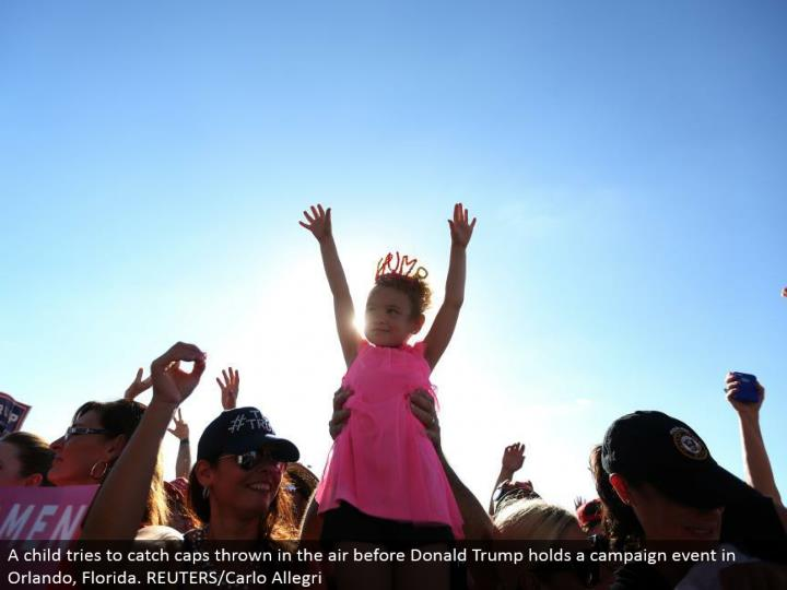 A kid tries to catch tops tossed noticeable all around before Donald Trump holds a battle occasion in Orlando, Florida. REUTERS/Carlo Allegri