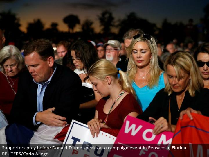 Supporters supplicate before Donald Trump talks at a battle occasion in Pensacola, Florida. REUTERS/Carlo Allegri