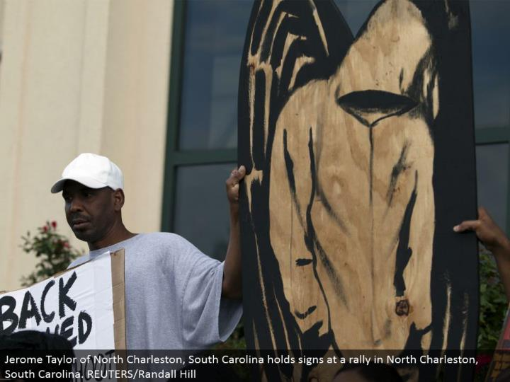 Jerome Taylor of North Charleston, South Carolina holds signs at a rally in North Charleston, South Carolina. REUTERS/Randall Hill